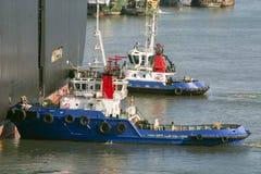 De boten die van de sleepboot een vrachtschip duwen aan haven Stock Afbeelding