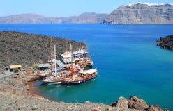 De boten van de toeristenexcursie bij kleine haven op vulkaan van Santorini Stock Foto's