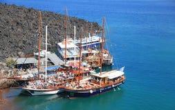 De boten van de toeristenexcursie bij kleine haven op vulkaan van Santorini Stock Foto