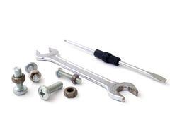 De bouten en de schroeven van de schroevedraaiermoersleutel op een wit Stock Foto