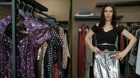 In de boutique, probeert een vrouw op een dazzlingly fonkelende lange rok stock footage