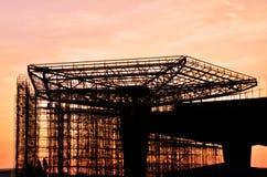 De bouw in aanbouw met zonsondergangachtergrond Stock Foto's