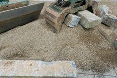 De bouw een steenmuur met rood graniet tijdens een baan van de landschapsbouw met een graafwerktuig en een klem die de grote sten stock fotografie