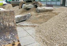 De bouw een steenmuur met rood graniet tijdens een baan van de landschapsbouw met een graafwerktuig en een klem die de grote sten stock foto's