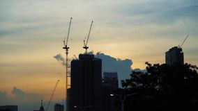 De bouw en kranen op de mooie hemelachtergrond bij zonsondergang Het de groei en ontwikkelingsconcept stock videobeelden
