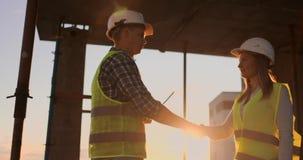 De bouw, groepswerk, vennootschap, gebaar en mensenconcept - sluit van bouwers indient omhoog handschoenen die elkaar begroeten stock video