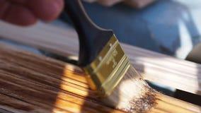 De bouw De houten stroken van de borsteldeklaag, houten vlek stock video