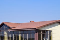 de bouw met gele muren en een roodbruin dak Moderne materialen van afwerking en dakwerk stock foto
