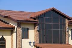 de bouw met gele muren en een roodbruin dak Moderne materialen van afwerking en dakwerk stock afbeelding