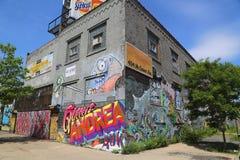 De bouw met muurschilderingen en graffiti in Williamsburg-sectie in Brooklyn wordt behandeld dat Stock Foto's