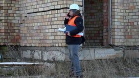 De bouw met smartphone dichtbij het gebouw stock video