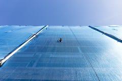 De bouw met steiger in het blauwe puin opleveren wordt gedrapeerd die Royalty-vrije Stock Foto
