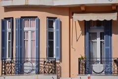 De bouw met witte vensters en blauwe koekoeken Stock Foto's