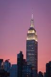De bouw van de imperiumstaat met heldere purpere hemel bij zonsondergang - de stad van New York Stock Foto's