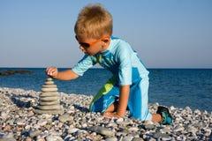 De bouw van de jongen steenstapel op strand Royalty-vrije Stock Foto