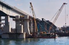 De bouw van een brug over de rivier trekt aan Stock Afbeelding