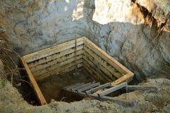 De bouw van een houten kelderverdieping in de opgegraven kuil Stock Foto's