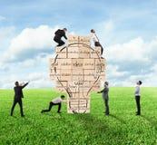 De bouw van een nieuw creatief idee De bedrijfspersoon bouwde samen een grote bakstenen muur met getrokken lightbulb Stock Foto