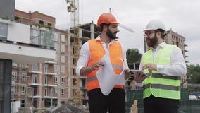 De bouw van een woon complex of commercieel centrum Team van ingenieursmensen met een tablet en een tekening die plannen analyser stock videobeelden