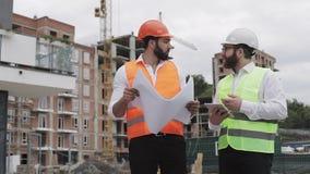 De bouw van een woon complex of commercieel centrum Team van ingenieursmensen met een tablet en een tekening die plannen analyser stock video