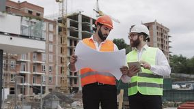 De bouw van een woon complex of commercieel centrum Team van ingenieursmensen met een tablet en een tekening die plannen analyser stock footage