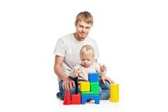 De bouw van het babymeisje van stuk speelgoed blokken met haar vader Stock Fotografie