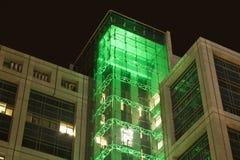 De bouw van het bureau bij nacht met groene lichten stock afbeelding