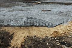 De bouw van het Parkeren voor bussen, het leggen van geomesh op grond vóór de asfaltbestrating, Rusland royalty-vrije stock afbeeldingen