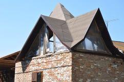 De bouw van huis met ingewikkeld dak Dakwerkbouw met het waterdicht maken van membraan stock foto