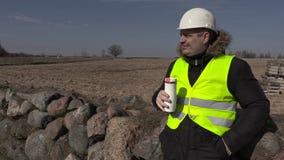 De bouw van inspecteur het drinken koffie dichtbij steenomheining stock video