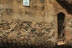 De bouw van voorgevel met gesloten deur en straatnaamteken in Caceres stock foto's