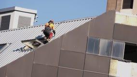 De bouwconstructie De arbeider op het dak stock videobeelden