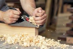 De bouwer behandelt een houten de hefboomvliegtuig van de plankraad royalty-vrije stock afbeelding