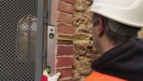 De bouwer controleert het deurniveau stock videobeelden