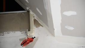 De bouwer of de arbeider verfraaien muur in wit stock videobeelden