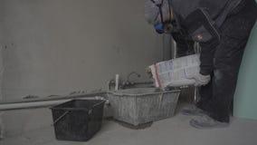 De bouwer in een ademhalingsapparaat valt in slaap in een container droog bouwmateriaal stock videobeelden