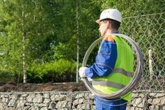 De bouwer in een witte helm draagt een streng van draad op zijn schouder, achtermening stock afbeelding