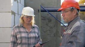 De bouwer en de klant inspecteren binnen het gebouw in aanbouw in ruimten stock video