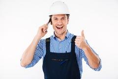 De bouwer in het algemene spreken op telefoon en het tonen beduimelt omhoog Royalty-vrije Stock Afbeelding