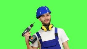 De bouwer houdt een boor in zijn handen en kijkt rond Het groene scherm stock videobeelden