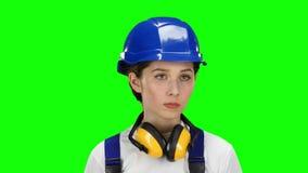De bouwer houdt een boor in zijn handen en kijkt rond Het groene scherm Sluit omhoog stock footage