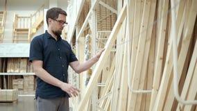 De bouwer koopt hout in de opslag stock footage