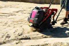 De bouwer met trillingsplaten verzegelt het basiszand voor het gieten van beton stock foto's