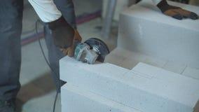 De bouwer overhandigt zagend gelucht concreet blok met cirkelzaag stock videobeelden