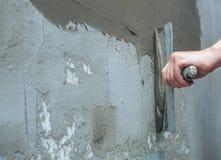 De bouwer zet de muur van de mortiertroffel Pleistermuren Buiten eindig royalty-vrije stock fotografie