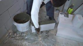 De bouwer zet zelfklevende oplossing aan kant van gelucht concreet blok met spatel stock footage
