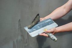 De bouwer zette mortier op de muur Pleistermuren Stock Foto