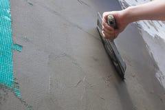 De bouwer zette mortier op de muur Pleistermuren Stock Afbeelding
