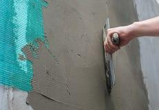 De bouwer zette mortier op de muur Pleistermuren Stock Afbeeldingen
