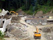 De bouwers banen de weg door het bos het werk van bulldozers stock afbeelding